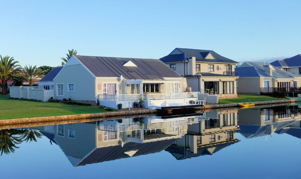 White single story houses beside body of water